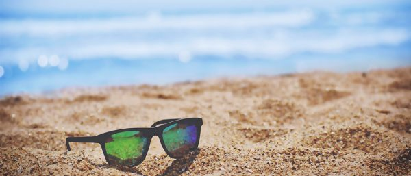 Sunglasses in the sand beside a blue sea.